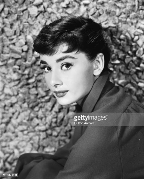 Portrait of Belgianborn American actress Audrey Hepburn as she sits by a stone wall early 1950s