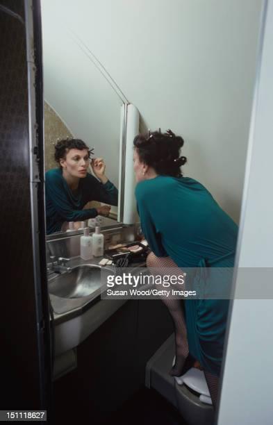 Portrait of Belgianborn fashion designer Diane von Furstenberg as she applies makeup in the mirror of an airplane restroom John F Kennedy Airport...