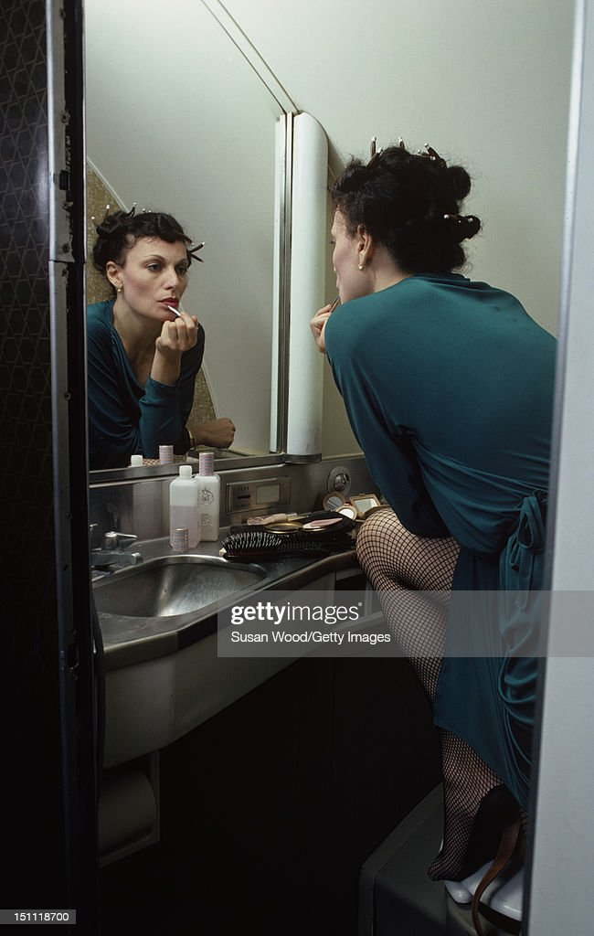 Portrait of Belgian-born fashion designer Diane von Furstenberg as she applies make-up in the mirror of an airplane restroom, John F. Kennedy Airport, Queens, New York, May 1979.