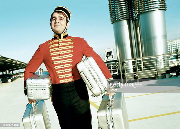 portrait of bellboy carrying suitcases