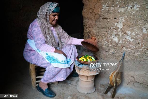 portrait of berber old woman in traditional dress watching tagine lunch cook on open fire, agounssan, high atlas, morocco (model release) - tajine fotografías e imágenes de stock