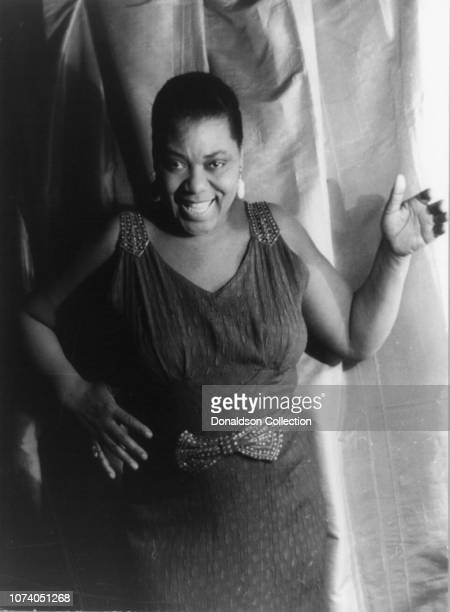 Portrait of Bessie Smith three quarter length portrait standing facing front with left hand raised