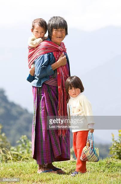 Portrait of Bhutanese woman and two children on hill, Timpu, Bhutan