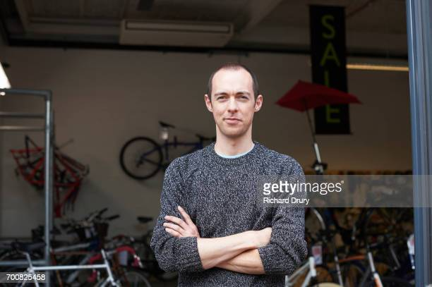 portrait of bicycle mechanic in shop - smirking stock pictures, royalty-free photos & images