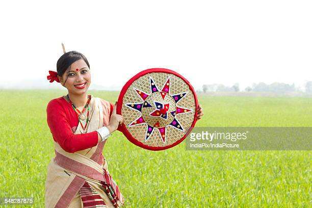 Portrait of Bihu woman holding a jaapi
