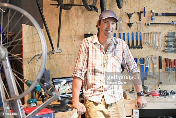 portrait of bike shop owner in his workshop