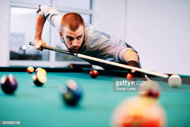 Portrait of billiard player aiming during tournament