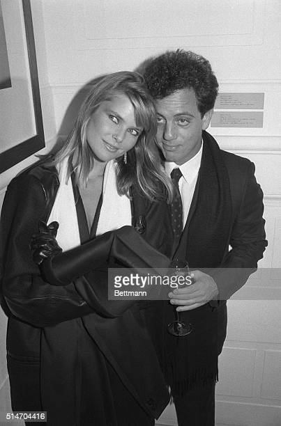 A portrait of Billy Joel and Christie Brinkley having a glass of wine while attending an exhibit at the International Center for Photography in New...