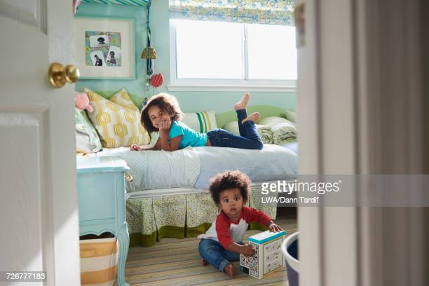 Portrait of Black brother and sister in bedroom
