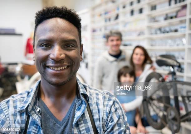 Portrait de la propriétaire de son magasin de vélo regardant sourire caméra noir