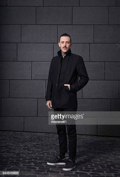 portrait of black dressed man in front of grey background - black coat stock photos and pictures