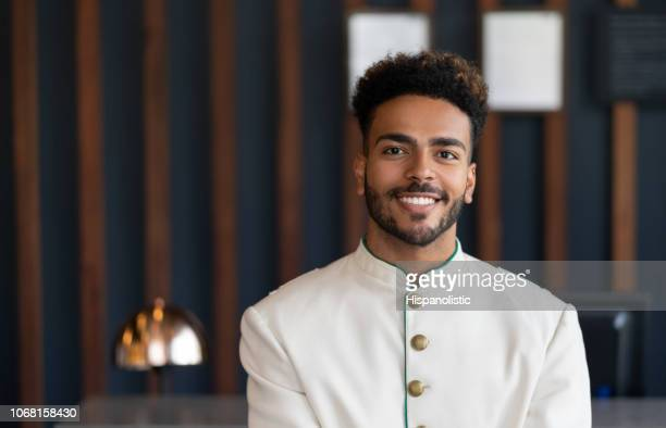 Portrait of black friendly bellhop working at hotel looking at camera very happy