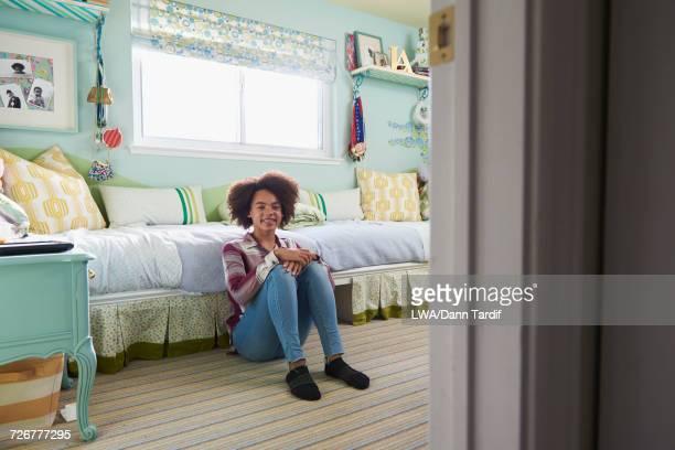 Portrait of Black girl sitting on floor in bedroom