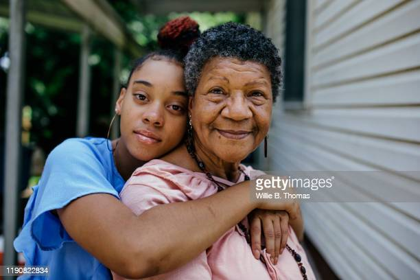 portrait of black grandmother with teenager granddaughter - simple living stock pictures, royalty-free photos & images