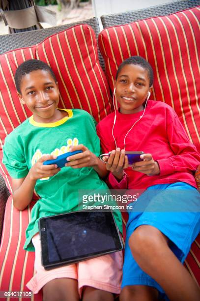 Portrait of Black twin boys using cell phones outdoors