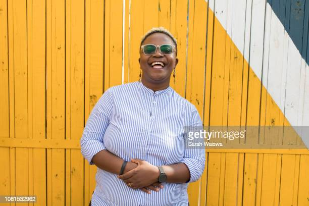 portrait of black woman in front of a yellow wall laughing - showus stock pictures, royalty-free photos & images