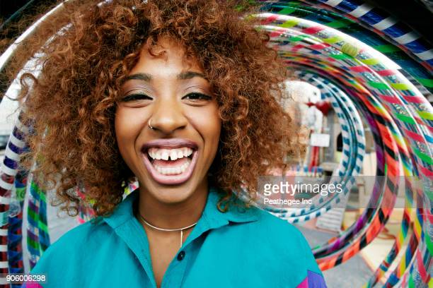 portrait of black woman laughing near hoops - nose piercing stock pictures, royalty-free photos & images