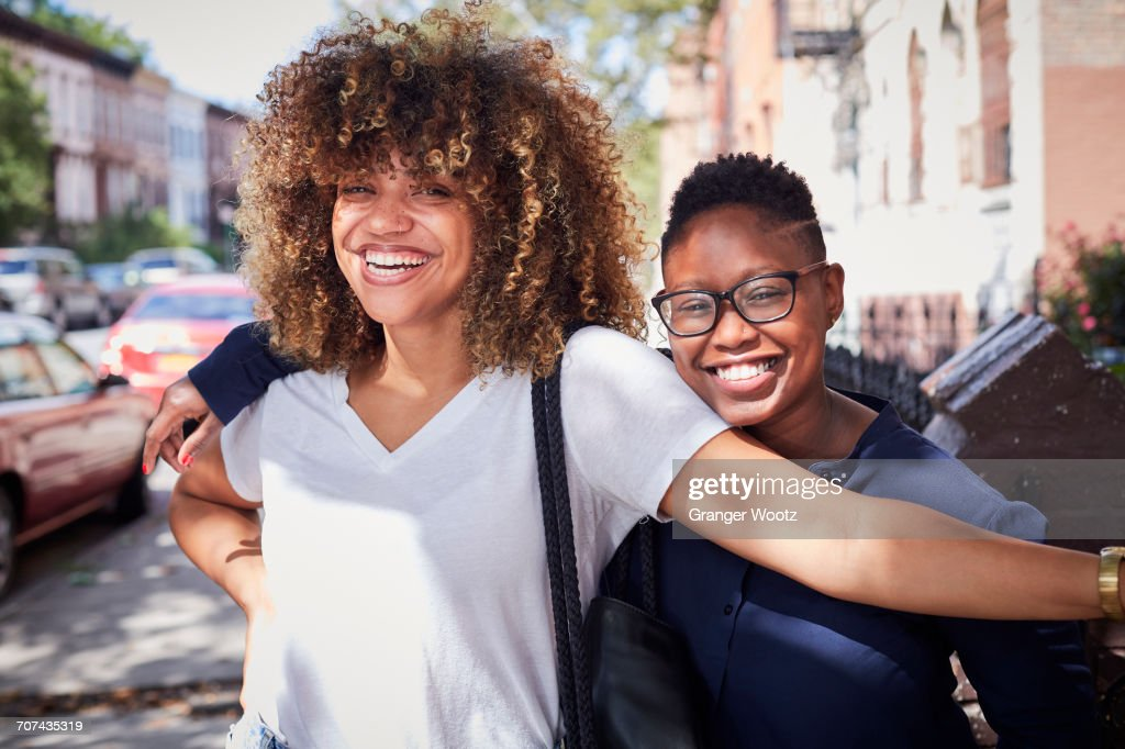 Portrait of Black women hugging on city sidewalk : Stock Photo