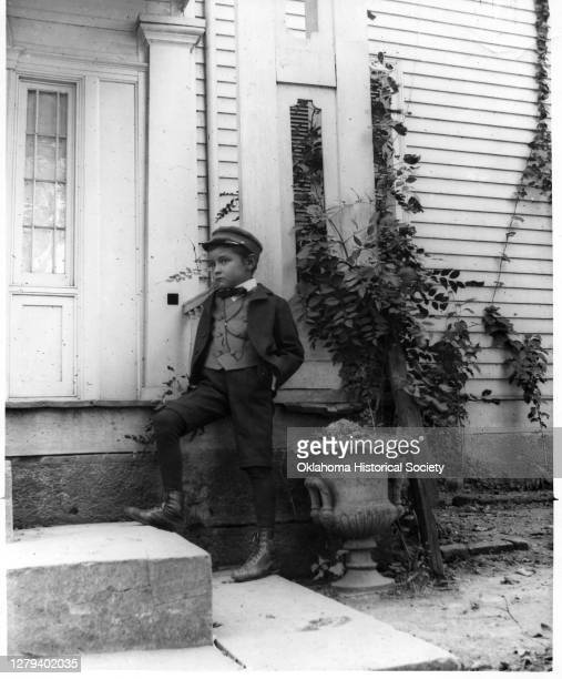 Portrait of Blake Ross as he poses, hands in his pockets, outside the George M Murrell Home , Park Hill, Indian Territory, early 1900s.