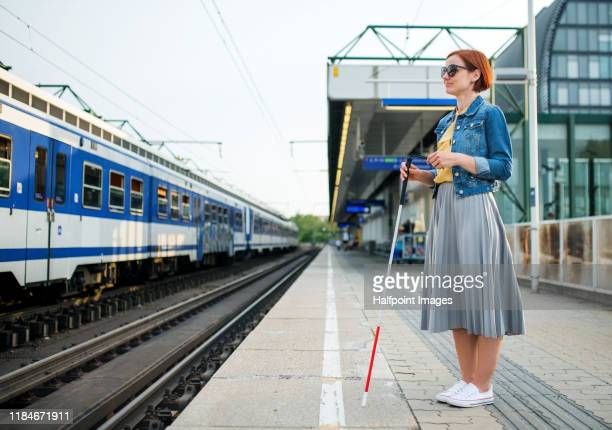 portrait of blind woman with white cane standing on train station outdoors in city. - 盲目 ストックフォトと画像