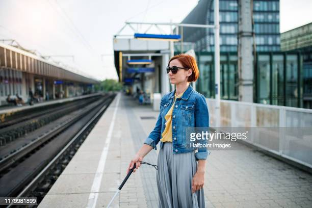 portrait of blind woman with white cane standing outdoors in city. - 視覚障害 ストックフォトと画像