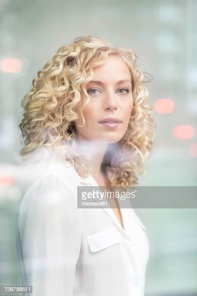 Portrait of blond businesswoman behind windowpane