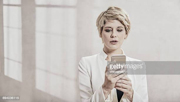 Portrait of blond businesswoman looking at cell phone