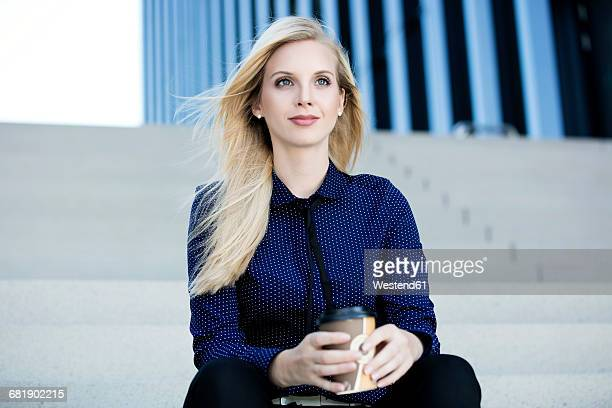 portrait of blond businesswoman sitting on stairs with coffee to go - one young woman only stock pictures, royalty-free photos & images