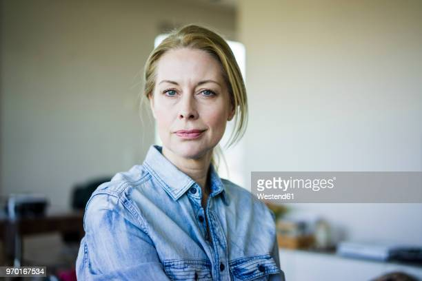 portrait of blond businesswoman wearing denim shirt - serious stock pictures, royalty-free photos & images