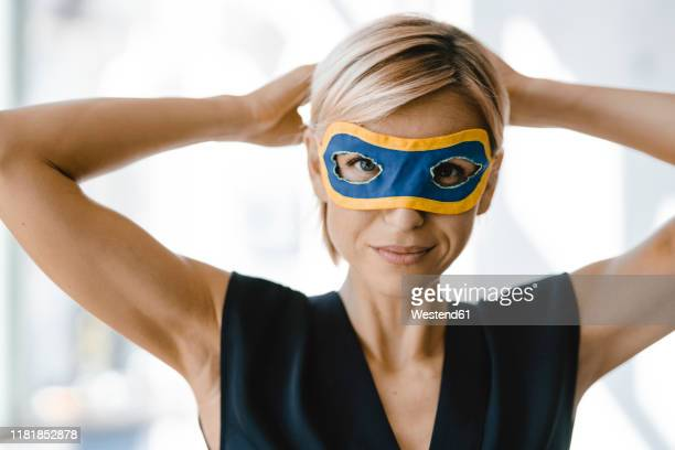 portrait of blond businesswoman, wearing superwoman mask - superhero stock pictures, royalty-free photos & images
