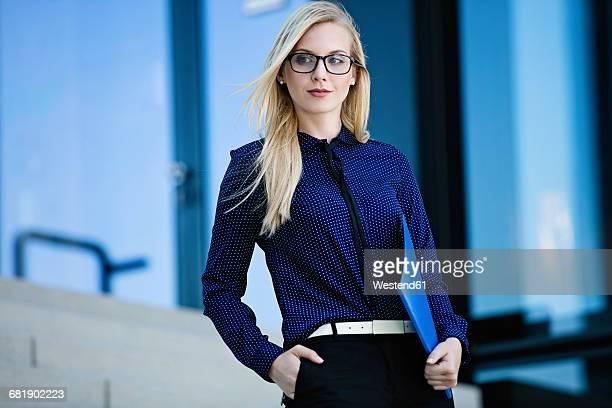 Portrait of blond businesswoman with folder