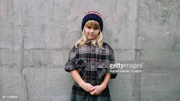portrait of blond girl standing against concrete wall - rolled up sleeves stock pictures, royalty-free photos & images