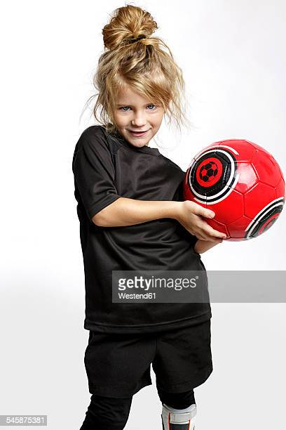 Portrait of blond girl with red soccer ball wearing football sportswear in front of white background