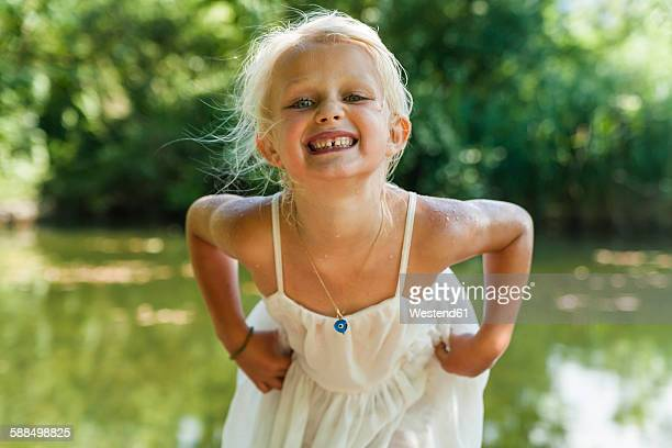 portrait of blond girl with wet dress at a lake - little girls bent over stock photos and pictures