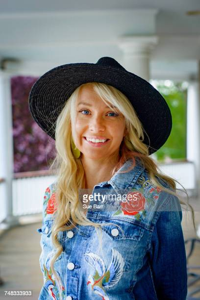 portrait of blond haired woman in cowboy hat on porch - tradition stock pictures, royalty-free photos & images