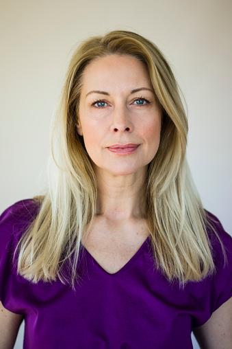 Portrait of blond mature woman wearing purple top - gettyimageskorea