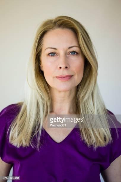 Portrait of blond mature woman wearing purple top