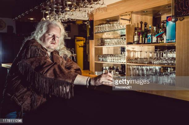portrait of blond rocker wearing brown leather jacket standing at counter of an old-fashioned pub - bar stock-fotos und bilder