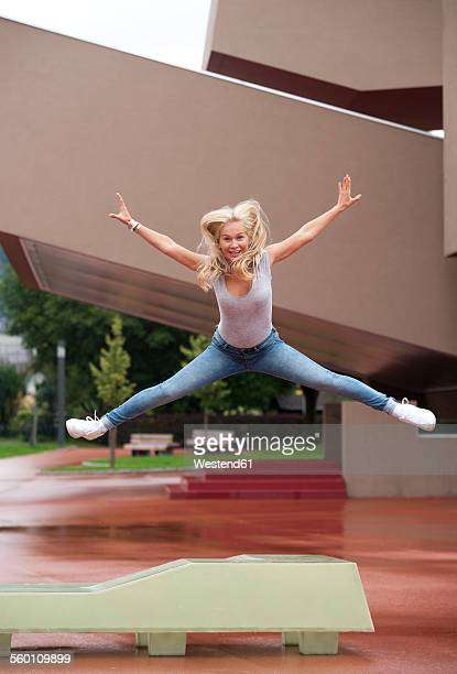 portrait of blond teenage girl jumping in the air with outstretched arms and legs - letter x stock pictures, royalty-free photos & images