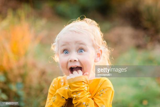 portrait of blond toddler girl with blue eyes pulling funny faces - starren stock-fotos und bilder