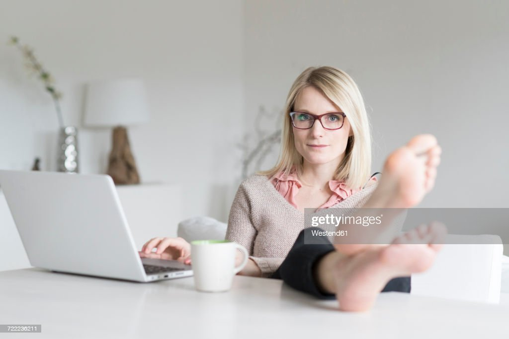 Portrait of blond woman at home sitting at table with feet up : Stock Photo