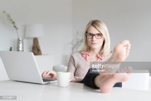portrait of blond woman at home sitting at table with feet up - female feet soles stock photos and pictures