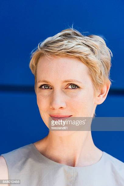 Portrait of blond woman in front of blue background