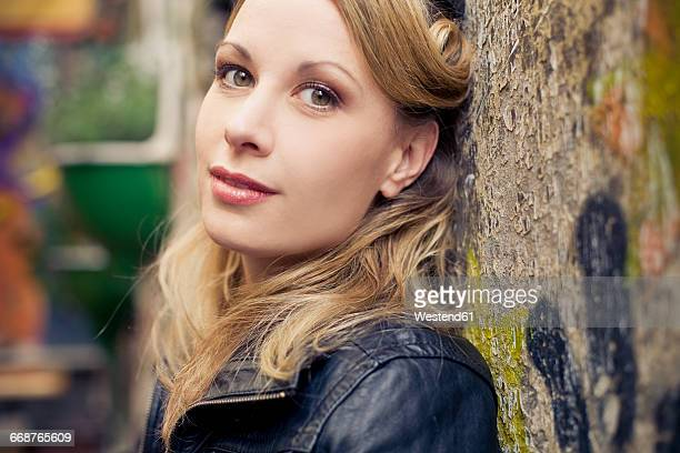 portrait of blond woman leaning against wall - seduction stock pictures, royalty-free photos & images