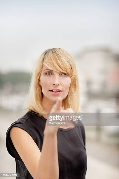 Portrait of blond woman pointing on viewer