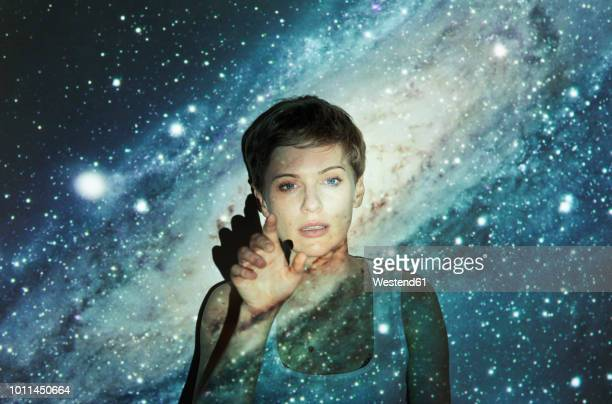portrait of blond woman, projection of milky way, imaginary touchscreen - traumhaft stock-fotos und bilder