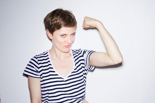 Portrait of blond woman, short hair, showing muscles - gettyimageskorea
