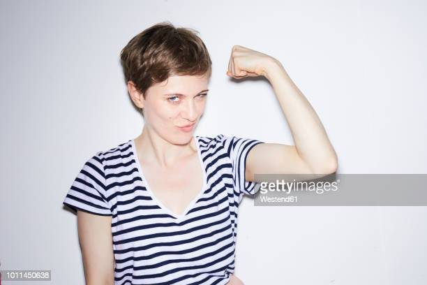 portrait of blond woman, short hair, showing muscles - human arm stock-fotos und bilder
