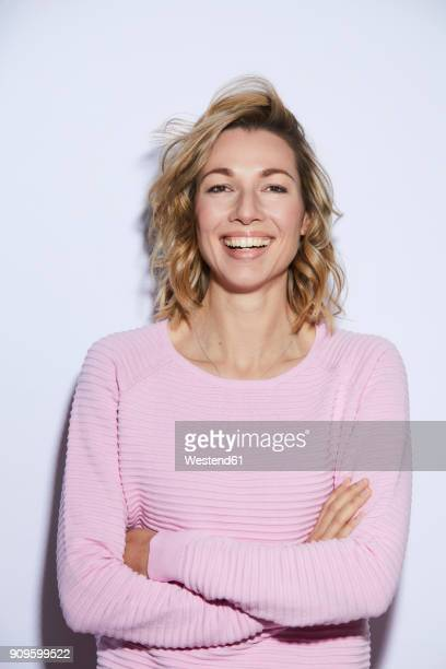 portrait of blond woman, smiling, rosa pullover - bovenlichaam stockfoto's en -beelden