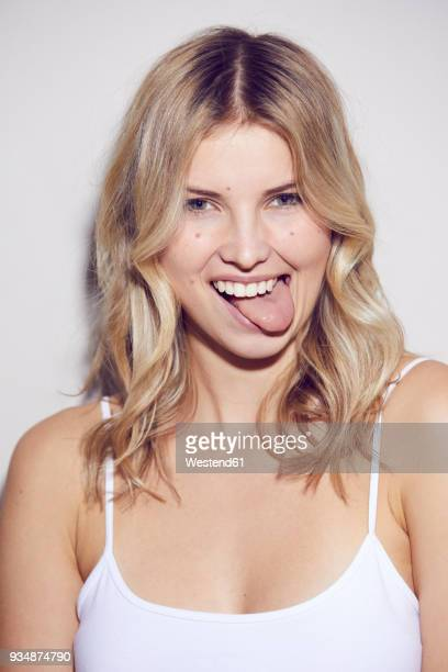 Portrait of blond woman sticking out tongue